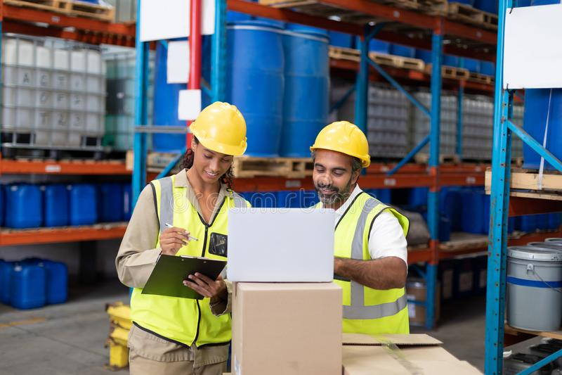 Male and female worker working together in warehouse. Front view of male and female worker working together in warehouse. This is a freight transportation and stock image