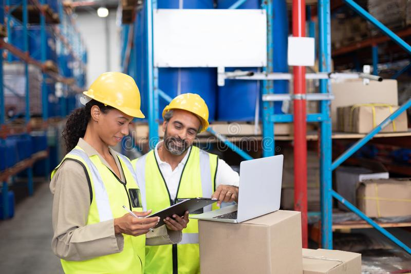Male and female worker working together in warehouse. Side view of male and female worker working together in warehouse. This is a freight transportation and royalty free stock photography