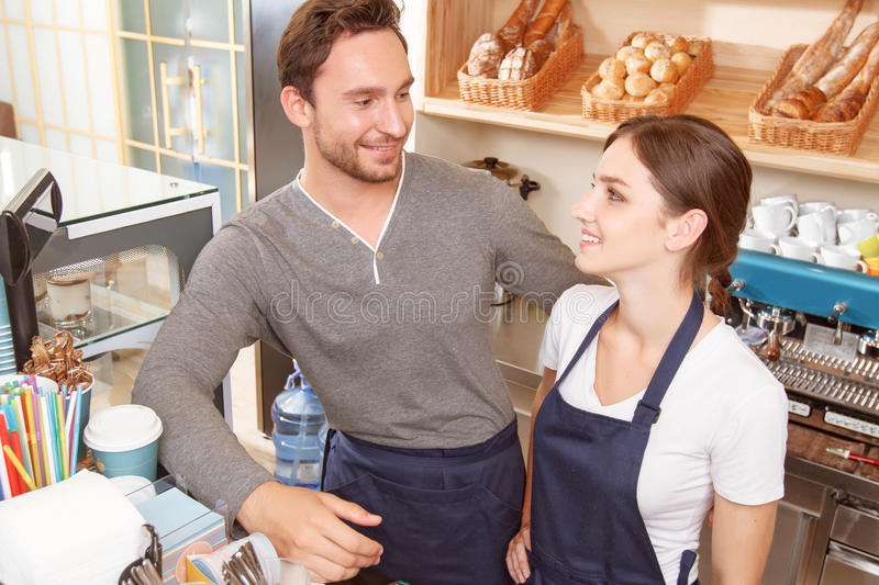 Male and female workers in cafe. Eye contact. Pair of cafeteria workers looking at each other during work stock images