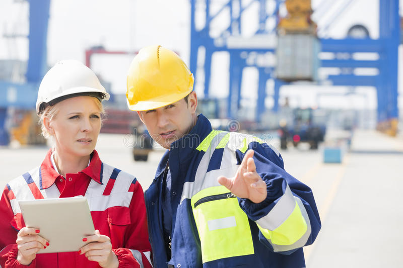Male and female workers discussing in shipping yard royalty free stock photos