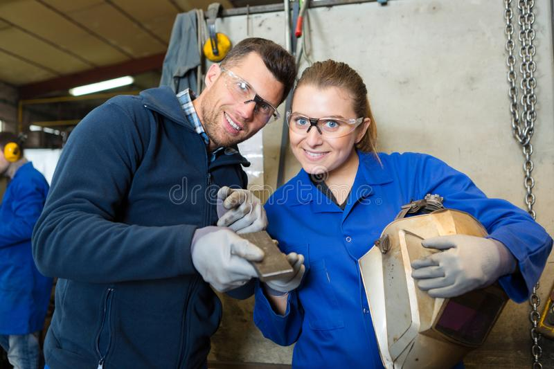 Male and female workers holding visor and piece metal. Male and female workers holding visor and piece of metal royalty free stock photos