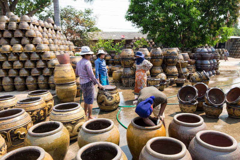 Male and female workers washing Dragon pattern flower pots.Focus at only male worker in front. stock image