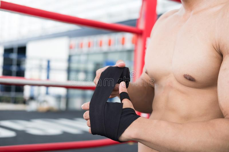 Male fighter wear bandages on fist. muscular man bind bandage on. Young male fighter wear bandages on fist. muscular man bind bandage on hand before training stock photos