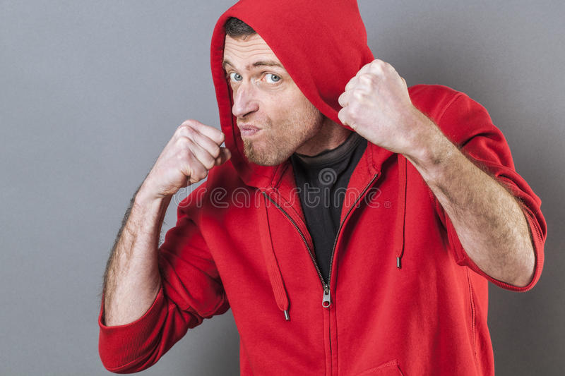 Male fighting concept for aggressive middle age rapper. Male fighting concept - aggressive middle age male rapper showing his fists for provocation or bullying royalty free stock images