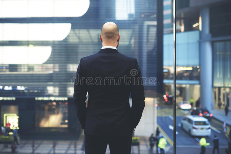 Male financier is resting after important meeting with international partners during business trip. Back view of man proud CEO in luxury suit is watching at big stock image