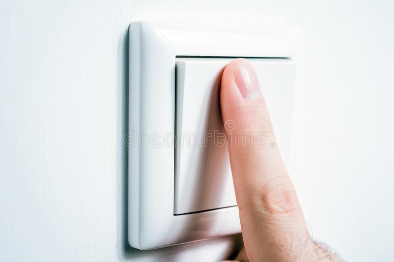 Male Finger Touching A Light Switch To Turn The Light On Or Off. A Male Finger Touching A Light Switch To Turn The Light On Or Off stock photo