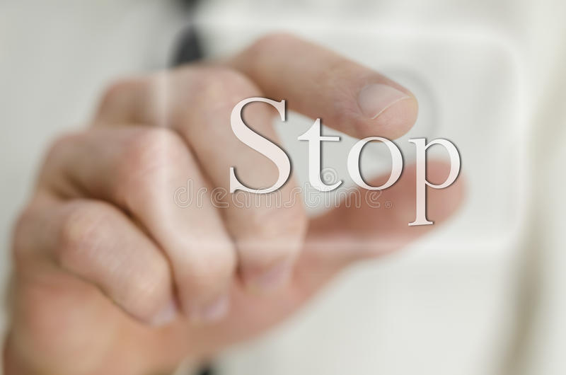 Male finger touching Stop button on a virtual screen. Detail of male finger touching Stop button on a virtual screen stock photo
