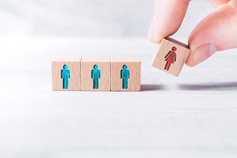 Male Fingers Adding A Block With A Different Colored Female Icon To 3 Blocks With Equal Colored Man Icons On A Table - royalty free stock photography