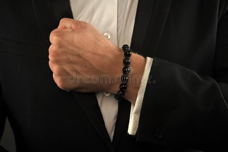 Male fist with bracelet on formal suit background. Bracelet or amulet on wrist. Amulet concept. Hand of business person. With amulet made out of black beads royalty free stock photography