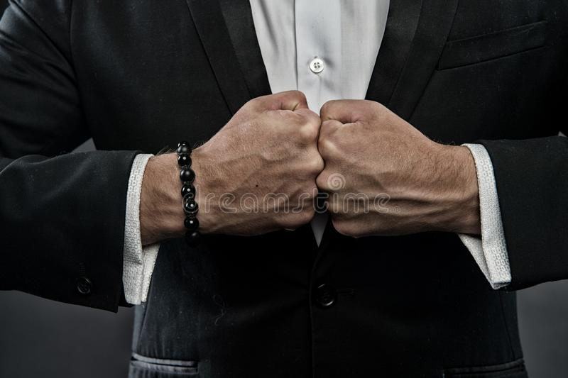 Male fists with swollen veins and bracelet on formal suit background. Confrontation concept. Hand of business person stock images