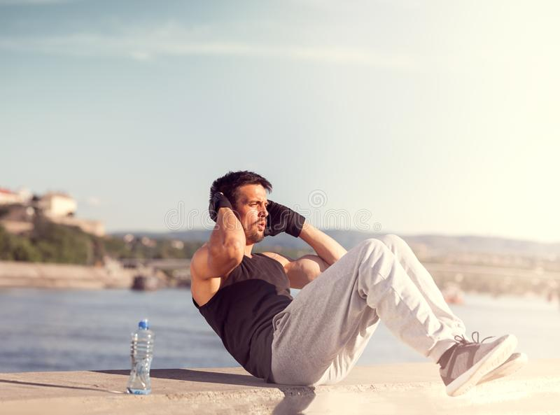 Male fitness model doing sit ups and crunches exercising abdominal muscles. Male fitness model in urban area on wall doing sit ups and crunches exercising stock photo