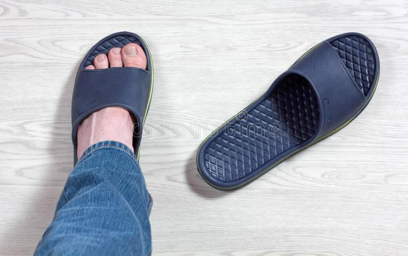 Male Foot Wearing a Slipper. Male foot wearing a blue slipper with the other slipper beside royalty free stock photography