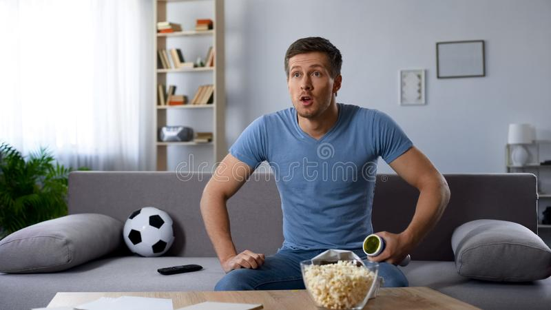 Male football fan sitting on sofa watching match on tv supporting favourite team. Stock photo stock photo