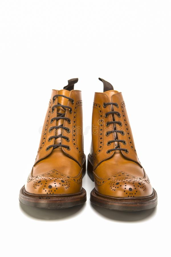 Male Footwear Ideas. Pair of Premium Tanned Brogue Derby Boots. Made of Calf Leather with Rubber Sole. Isolated Over Pure White Background. Vertical Image royalty free stock image