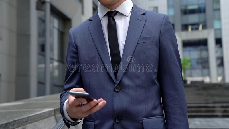 Male in formalwear reading news on smartphone, using business applications. Stock photo stock images