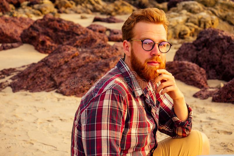 Male freelancer bearded glasses hipster with a laptop remote work on the beach on the sunset.freelancing guy working. Near the rocks and the sea.business man on stock photo