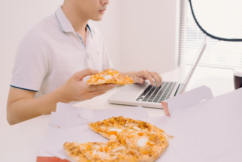 Male freelancer eating pizza while working  at home office stock photography