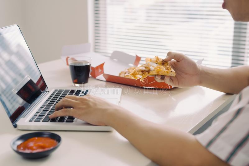Male freelancer eating pizza while working at home office royalty free stock image