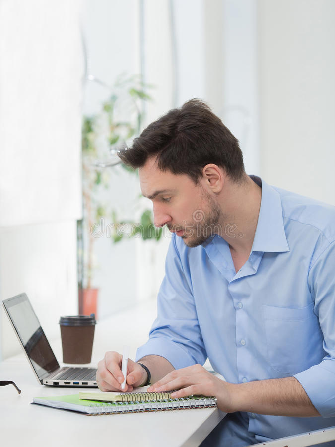 Male freelancer write message. Handsome male freelancer looking laptop computer's screen and writing information in notebook. Man working in office or restaurant royalty free stock photography