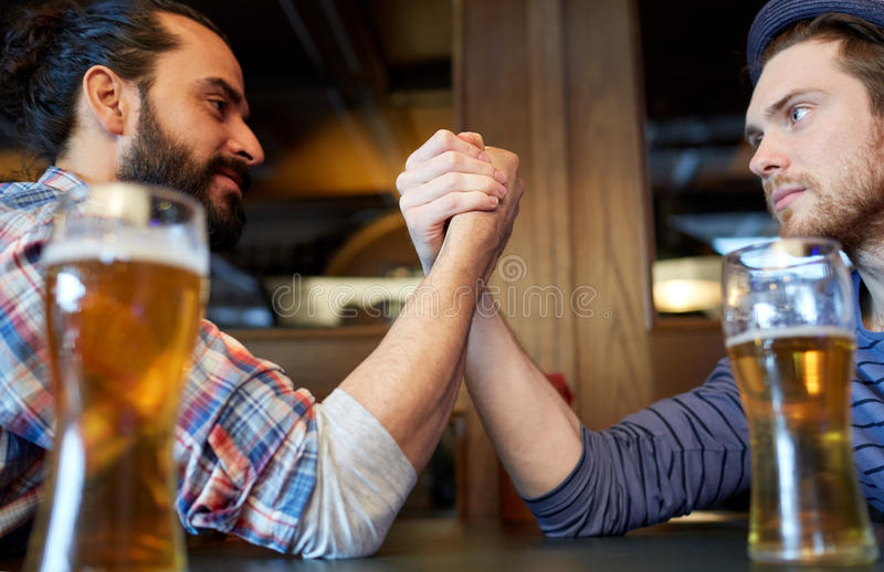 Male friends arm wrestling at bar or pub. People, leisure, challenge, competition and rivalry concept - male friends arm wrestling and drinking draft beer at bar royalty free stock photos