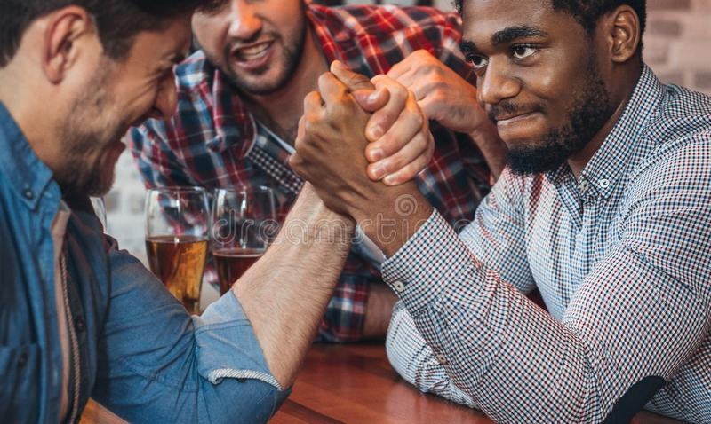 Male friends arm wrestling each other in bar royalty free stock photography
