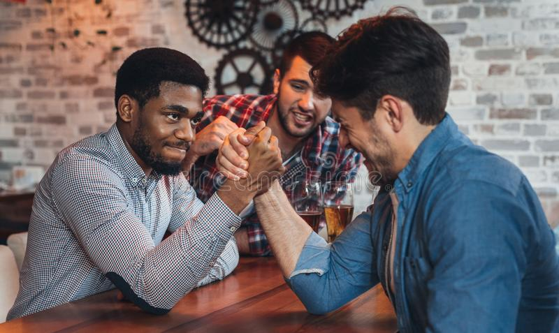 Male friends arm wrestling each other in bar stock photo