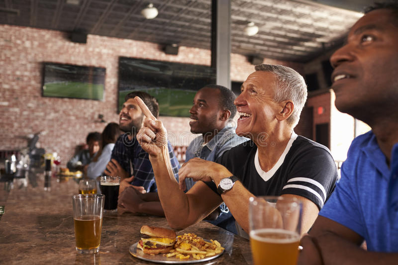 Male Friends At Counter In Sports Bar Watching Game royalty free stock photos