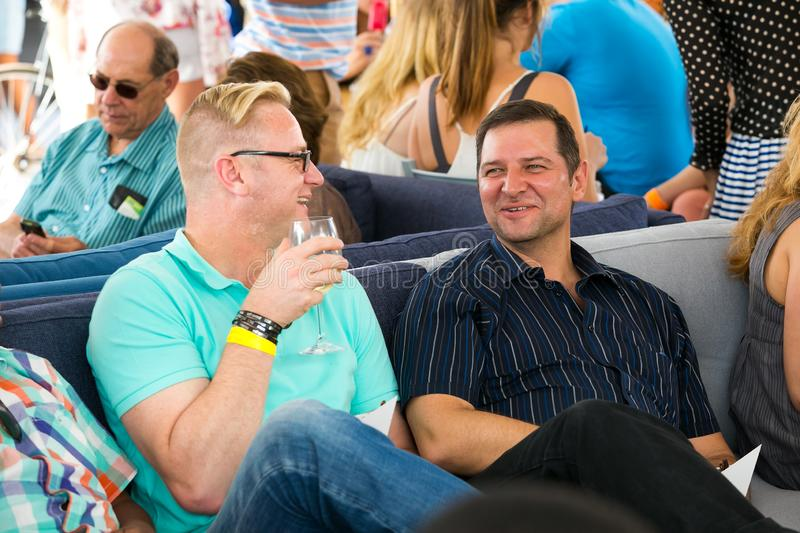 Male Friends drinking and generally enjoying a day out at a Food and Wine Fair drinking and generally enjoying a day out at a Food. Johannesburg, South Africa royalty free stock image