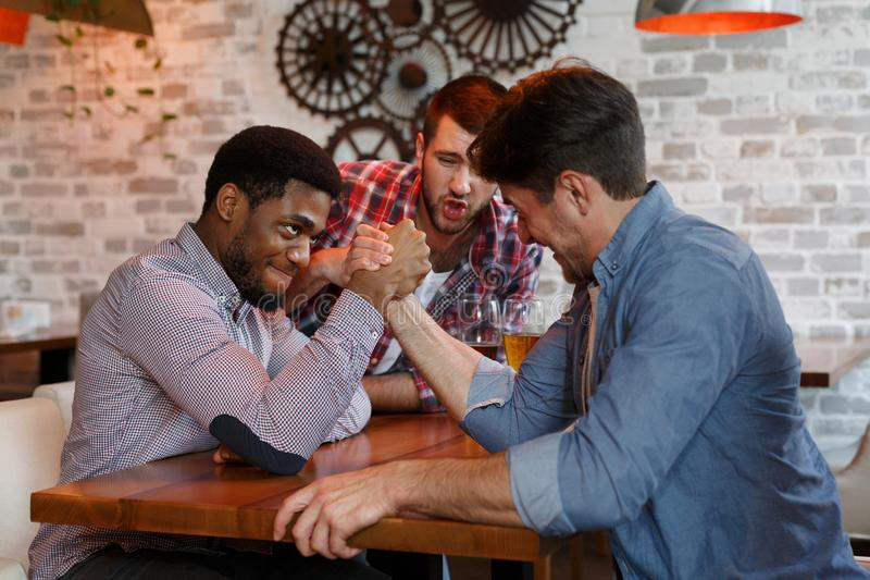 Male Friends Having Fun, Arm Wrestling And Drinking Beer. In Bar royalty free stock photos