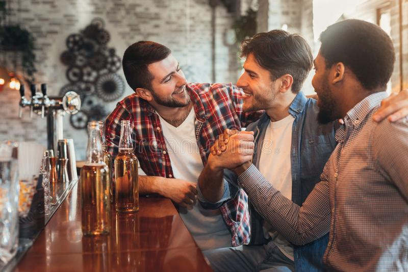 Male friends meeting in pub, drinking beer stock images