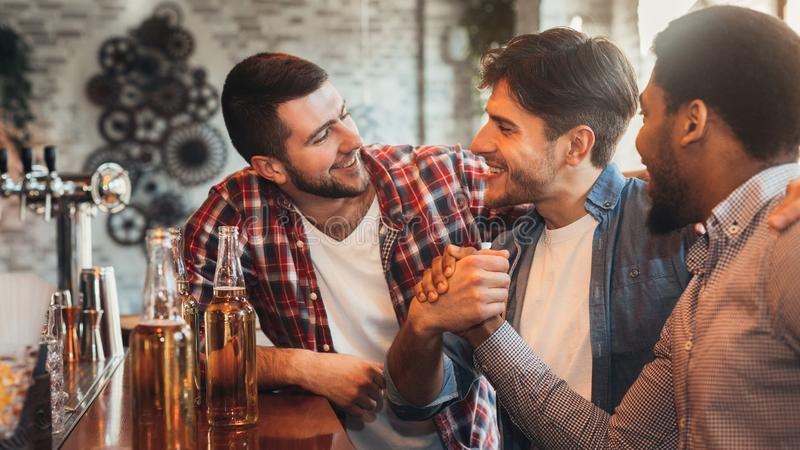 Male friends meeting in pub, drinking beer royalty free stock photo