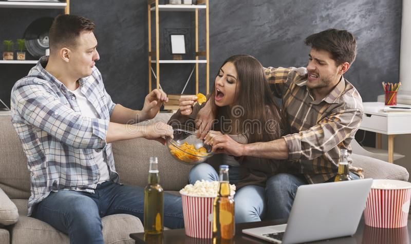 Male friends playfully fighting with their female friend over snacks royalty free stock photos