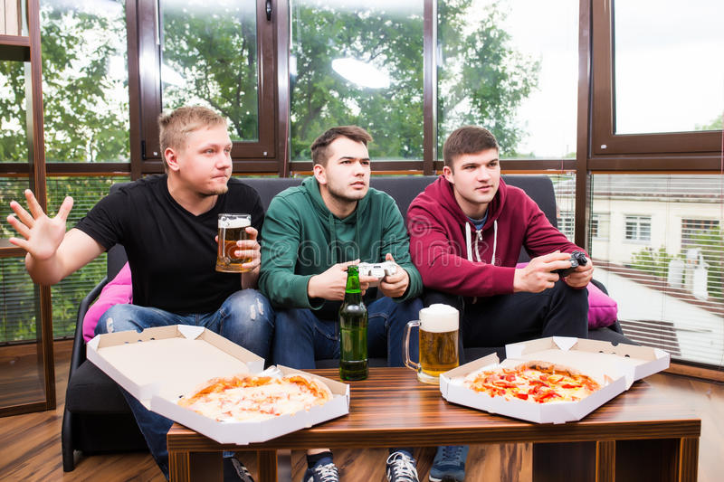 Male friends playing video games, drink beer and have fun at home. Friendship, technology, games and home concept - smiling male friends playing video games royalty free stock image