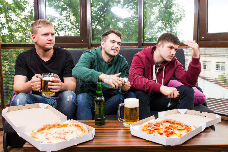 Male friends playing video games, drink beer and have fun at home. Friendship, technology, games and home concept - smiling male friends playing video games royalty free stock photography