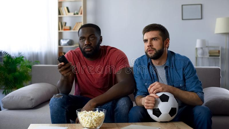 Male friends watching american football match, trying to understand rules stock image