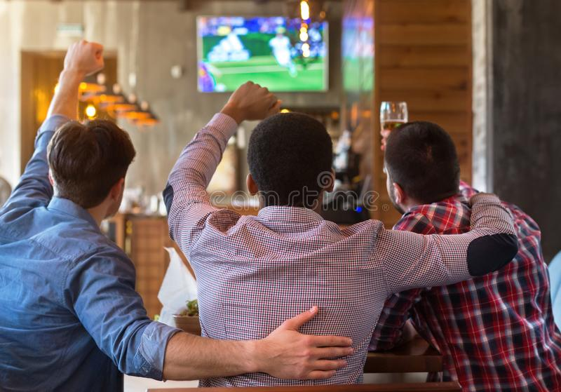 Male friends watching football match on TV in bar stock photography