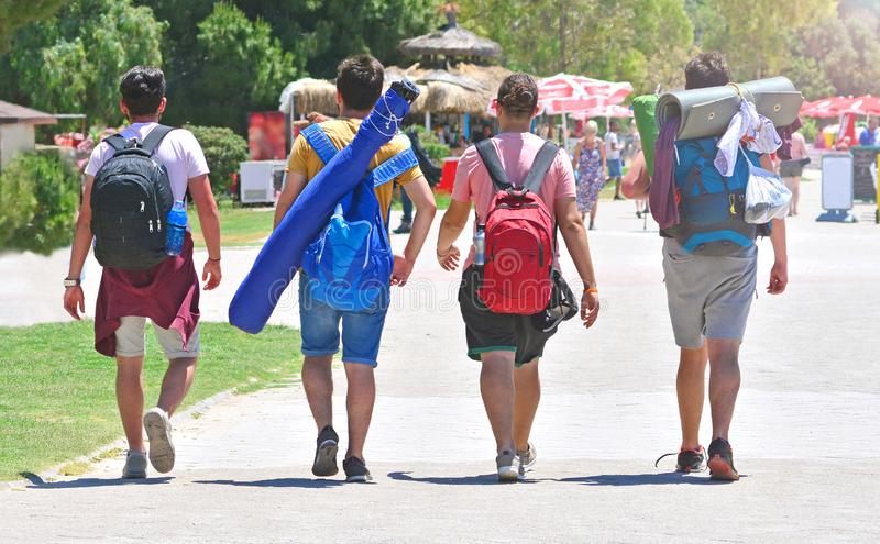 Male friendship concept. Four young guys with travel backpacks go on touristic place. Hike in summer day. Sun shines bright stock photo
