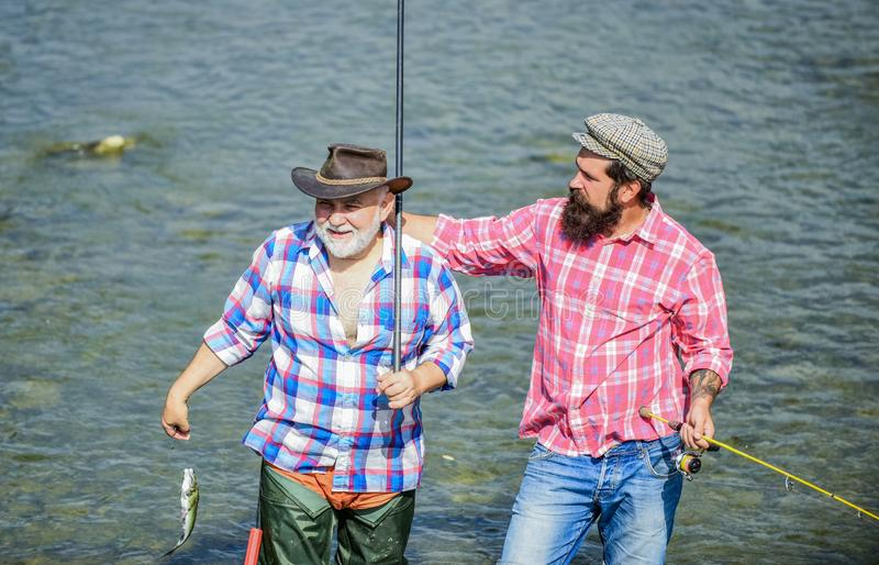 Male friendship. Men stand in water. Nice catch concept. Fishing team. Happy fisherman with fishing rod and net. Hobby stock photography