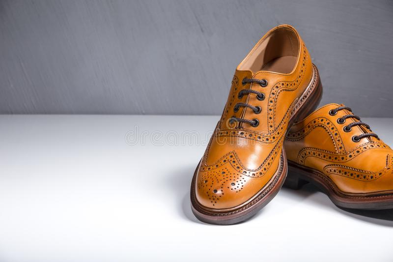 Male Full Broggued Tan Leather Oxfords Shoes. Luxury Male Full Broggued Tan Leather Oxfords Shoes Placed Over White Surface. Against Gray Wall. Horizontal Image royalty free stock photos