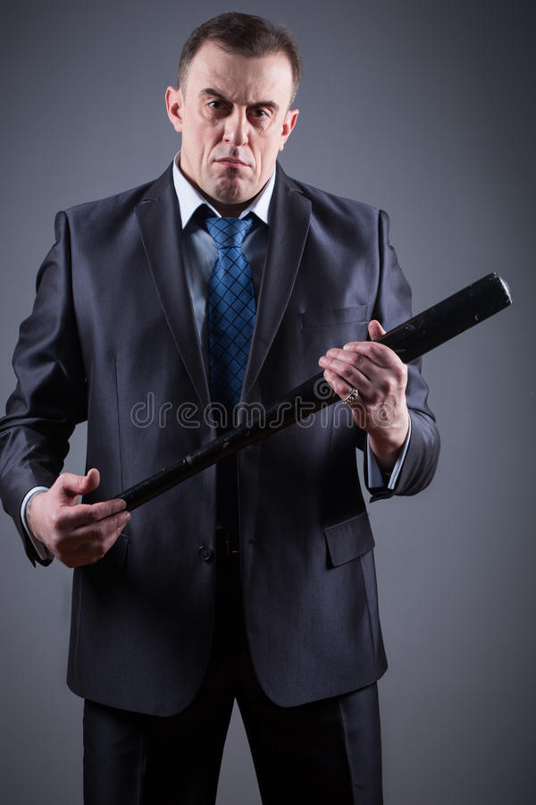 Male gangster with baseball bat. On a gray background stock image
