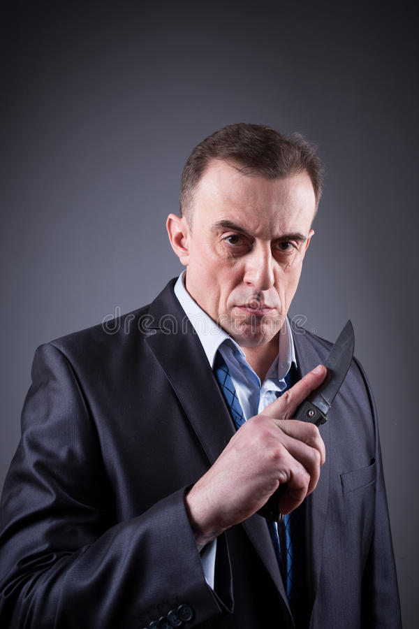 Male gangster in a business suit with a knife royalty free stock photography
