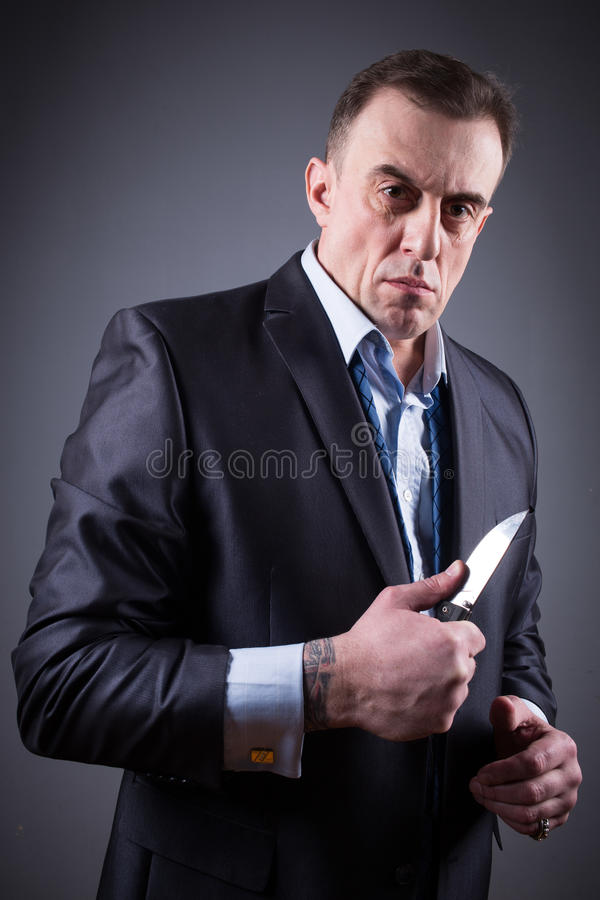 Male gangster in a business suit with a knife stock images