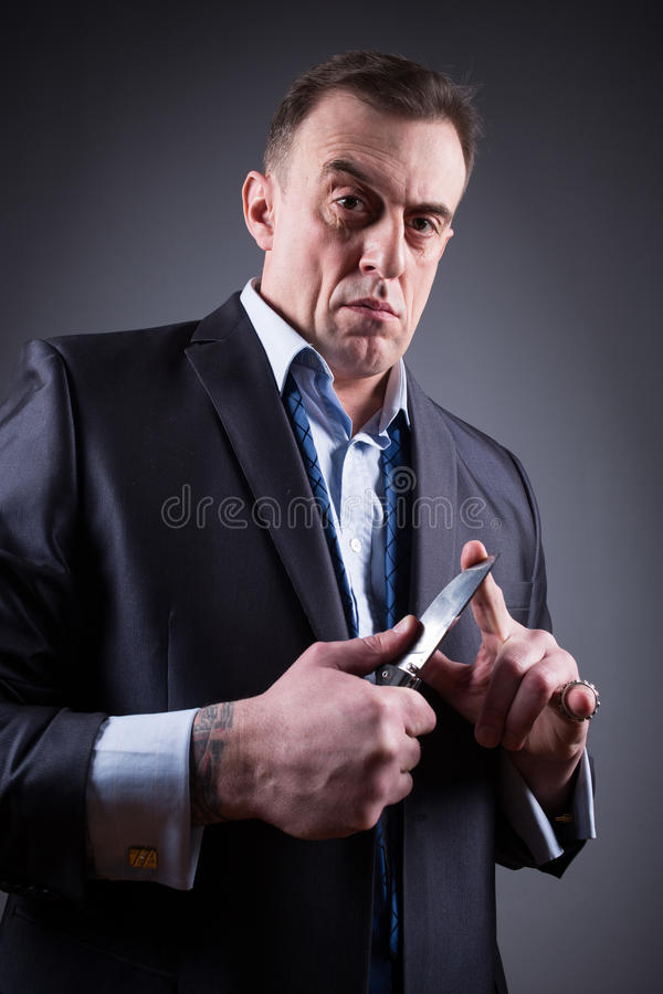 Male gangster in a business suit with a knife stock photo