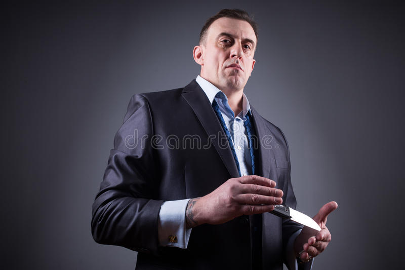Male gangster in a business suit with a knife stock image