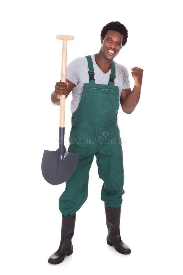 Male Gardener Holding Shovel. Happy Male Gardener Holding Shovel Over White Background stock image
