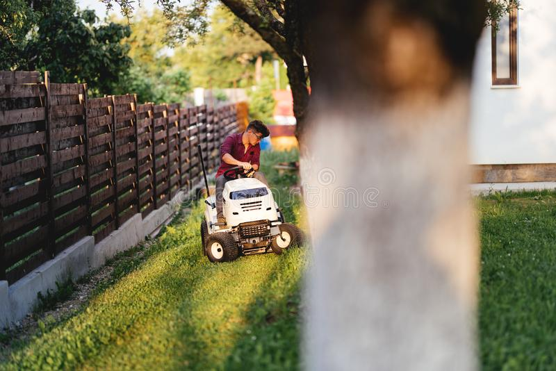 Male gardner riding lawn mower and trimming grass in garden. Male worker riding lawn mower and trimming grass in garden stock photography