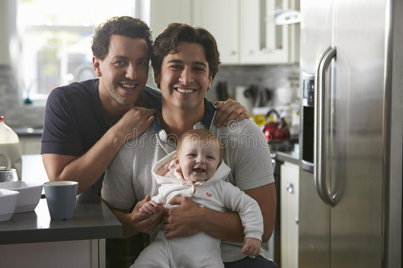 Male gay couple with baby girl in kitchen looking to camera royalty free stock photo