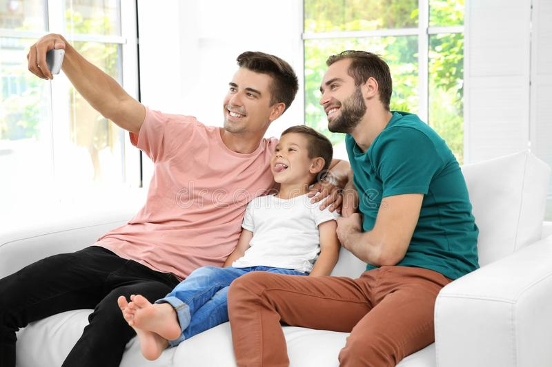 Male gay couple with foster son taking selfie. stock photography
