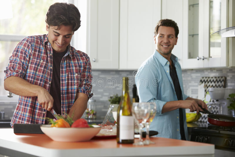 Male gay couple preparing a meal together in the kitchen royalty free stock image