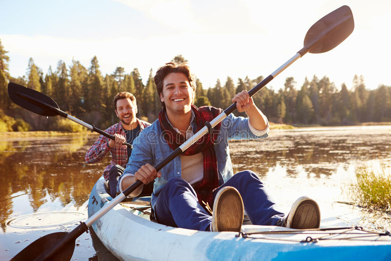 Male Gay Couple Rowing Kayak On Lake Together stock photo